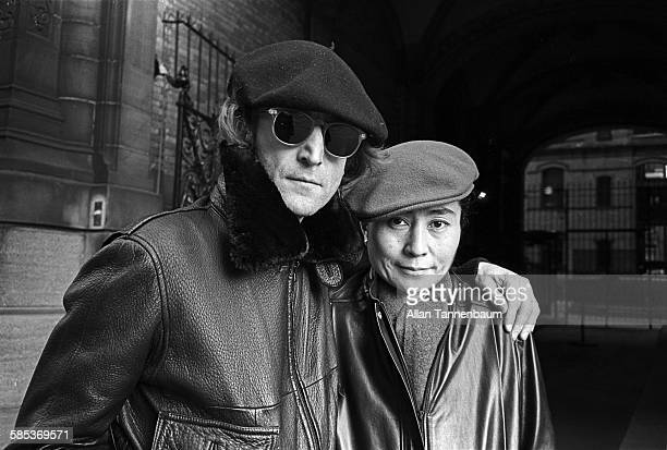 Portrait of married musicians John Lennon and Yoko Ono both in leather jackets and berets as they pose outside the Dakota Apartments where they lived...