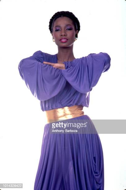 Portrait of fashion model Monia as she poses in a purple dress with a gold belt against a white background New York 1970s