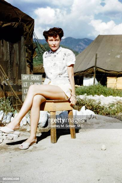 Portrait of Mary Jones on the neurosurgical team at the 8063rd MASH dressed in a newspaperprint top as she sits outside a US Army tent South Korea...