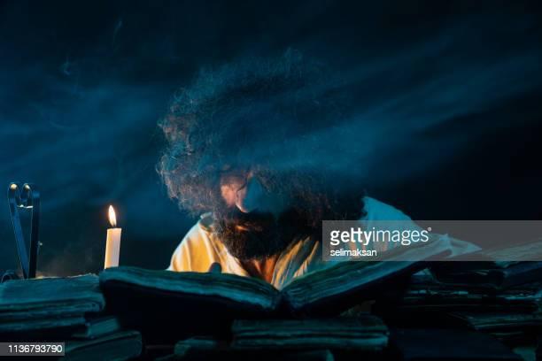 Retrato de hombre adulto maduro leyendo libro antiguo con luz de velas