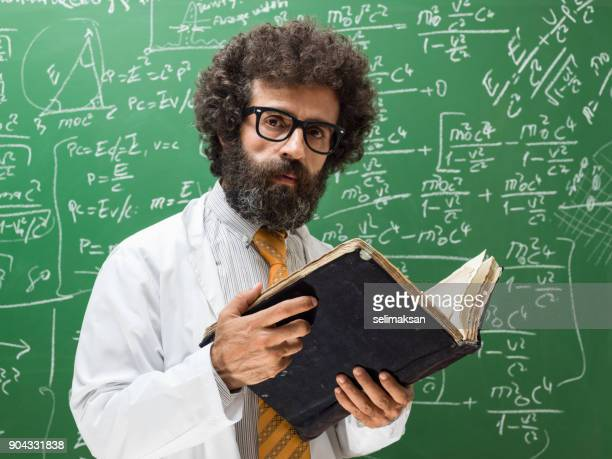 Portrait Of Mature Adult Man Wearing Lab Coat In Front Of Blackboard