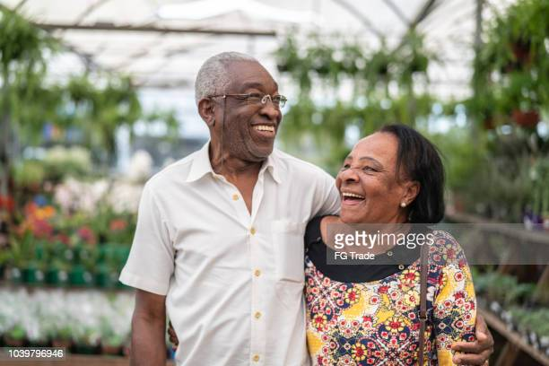 portrait of mature african couple customer at flower market - african american couple stock pictures, royalty-free photos & images