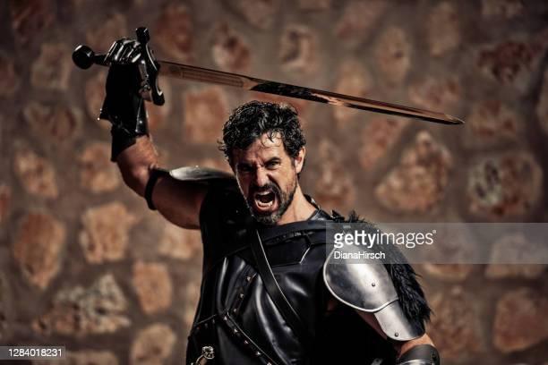 剣を持つ成熟した怒っているファンタジー中世の騎士の肖像 - 攻める ストックフォトと画像