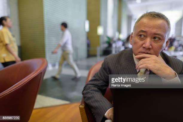 コーヒー ショップで休憩を持つ成熟したアジア系のビジネスマンの肖像画