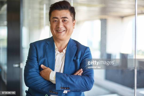 portrait of mature asian businessman smiling to camera - chinese ethnicity stock pictures, royalty-free photos & images