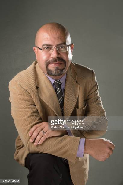 Portrait Of Mature Bald Businessman Standing Against Gray Wall