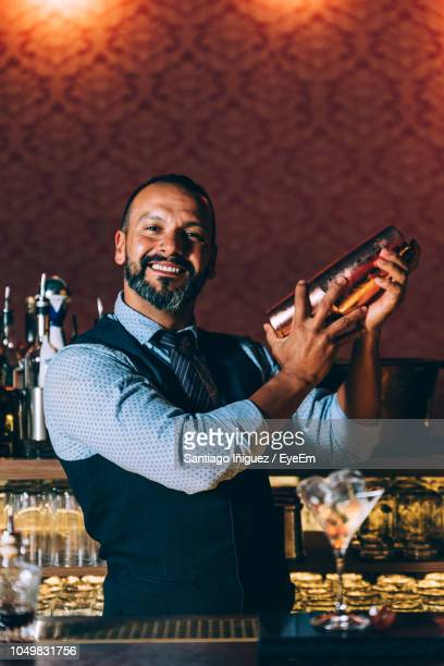 portrait of mature bartender preparing cocktail on bar counter - bartender stock pictures, royalty-free photos & images