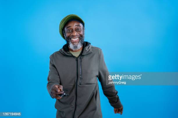 portrait of mature black man in knit hat and hooded jacket - one mature man only stock pictures, royalty-free photos & images