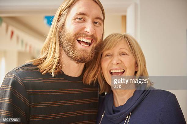 portrait of mature blond woman and adult son at home - older woman younger man stock photos and pictures