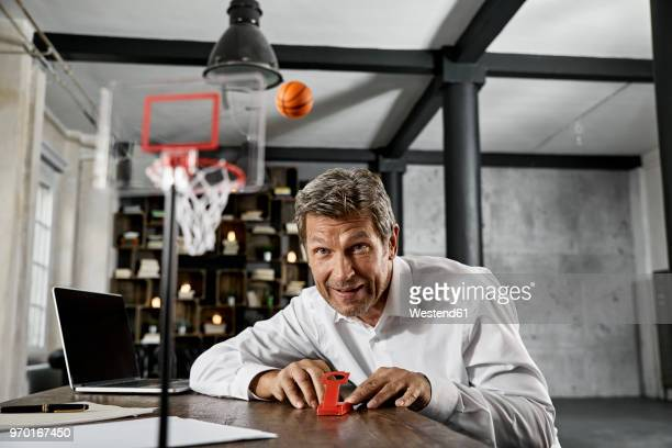 portrait of mature business man playing office games in loft - point scoring stock pictures, royalty-free photos & images
