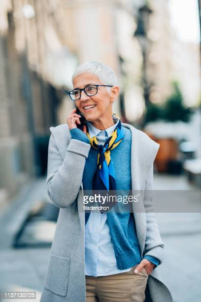 portrait of mature business woman talking on the phone - hands in pockets stock pictures, royalty-free photos & images