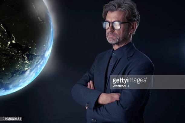 portrait of mature businessman against dark background watching floating planet earth - all shirts stock-fotos und bilder