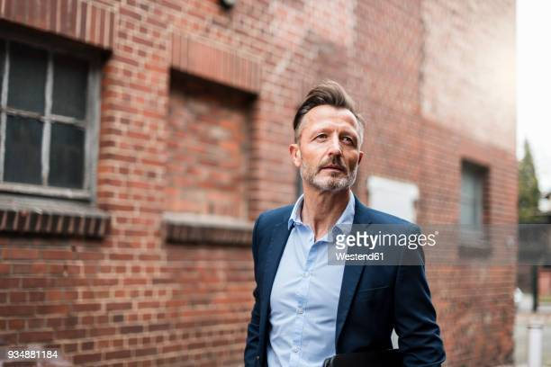 portrait of mature businessman at brick building - blazer chaqueta fotografías e imágenes de stock