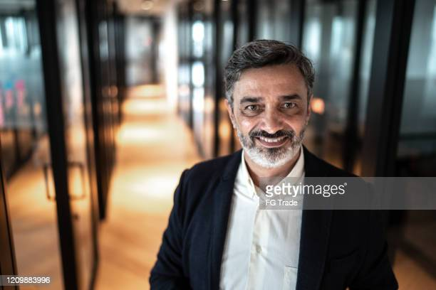 portrait of mature businessman at corridor office - founder stock pictures, royalty-free photos & images