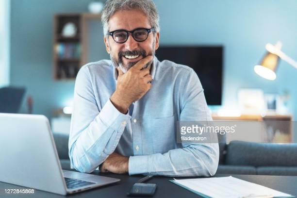 portret van rijpe zakenman thuis - flexplekken stockfoto's en -beelden