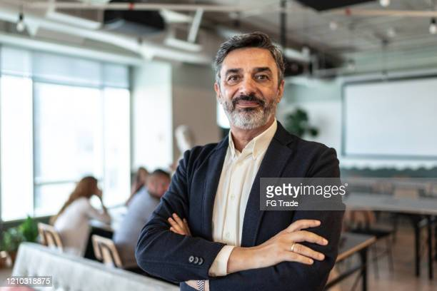 portrait of mature businessman at modern office - chief executive officer stock pictures, royalty-free photos & images