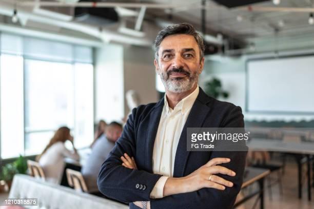 ritratto di uomo d'affari maturo in un ufficio moderno - solo un uomo maturo foto e immagini stock