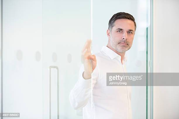 portrait of mature businessman at the door of his office - endast medelålders män bildbanksfoton och bilder