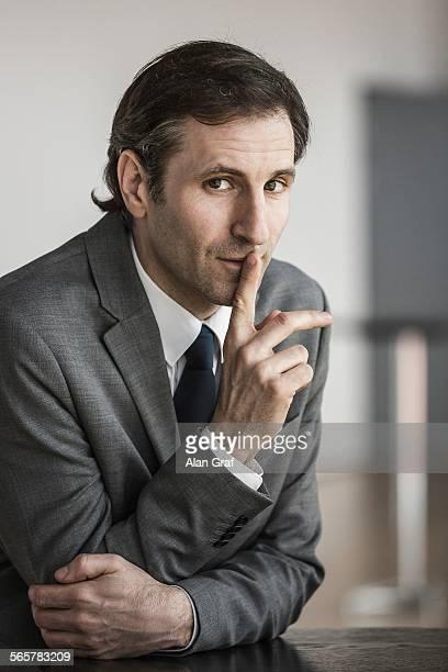 Portrait of mature businessman, finger to lips