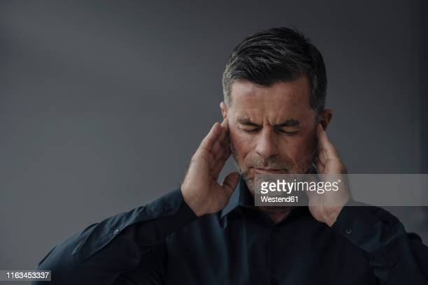 portrait of mature businessman having earaches - headache stock pictures, royalty-free photos & images