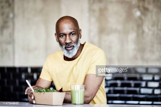 portrait of mature businessman having lunch break in office - desaturated stock pictures, royalty-free photos & images