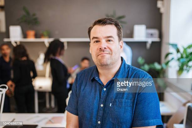 portrait of mature businessman in co-working space - chubby men stock photos and pictures