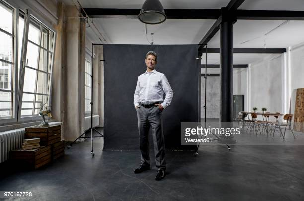 portrait of mature businessman in front of black backdrop in loft - males photos stock pictures, royalty-free photos & images
