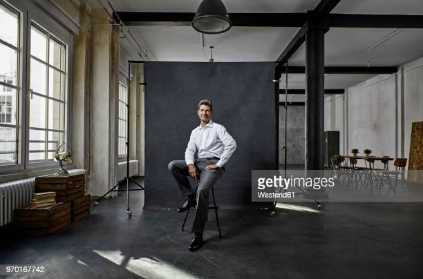 portrait of mature businessman in front of black backdrop in loft - projektion stock-fotos und bilder