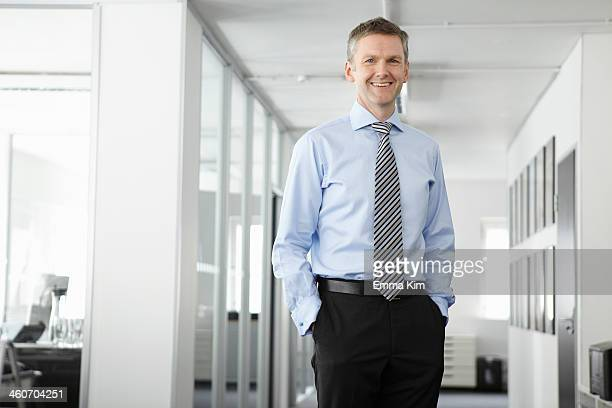 portrait of mature businessman in office, hands in pockets - krawatte stock-fotos und bilder