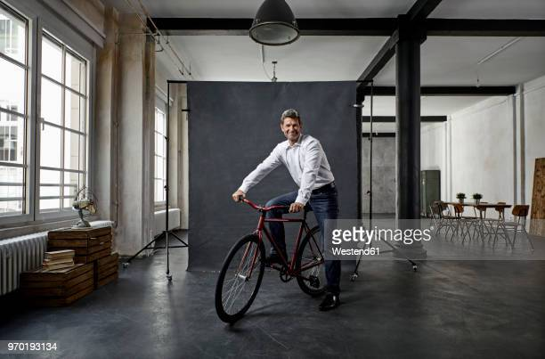 Portrait of mature businessman on fixie bike in front of black backdrop in loft