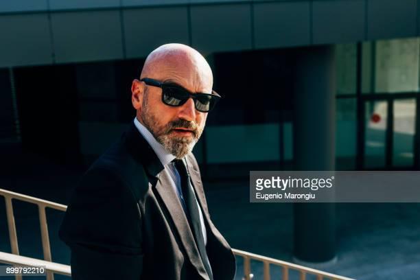 portrait of mature businessman outdoors, wearing sunglasses - solo un uomo maturo foto e immagini stock
