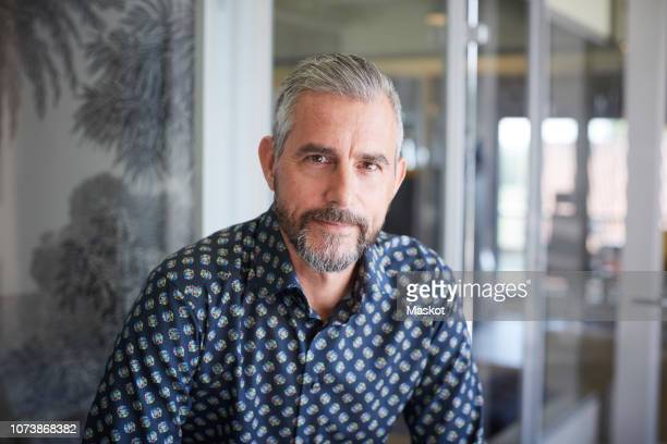 Portrait of mature businessman sitting in creative office