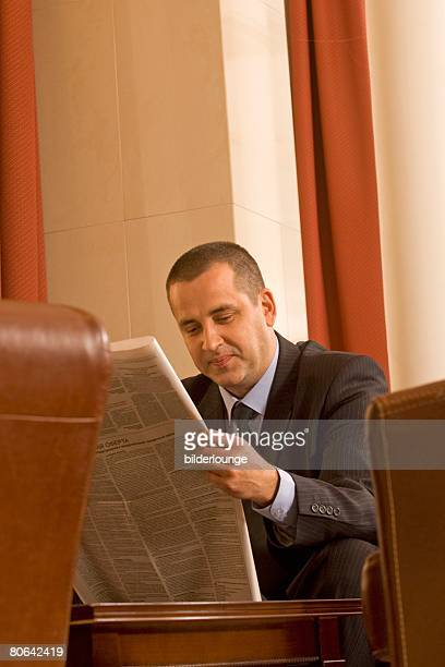portrait of mature businessman sitting in hotel lobby reading newspaper