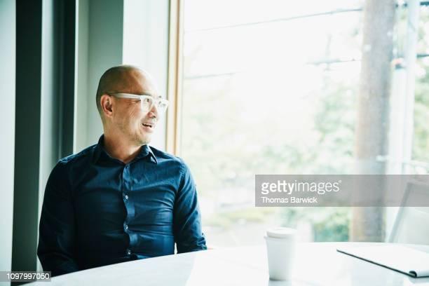 portrait of mature businessman sitting in office conference room looking out window - front view bildbanksfoton och bilder