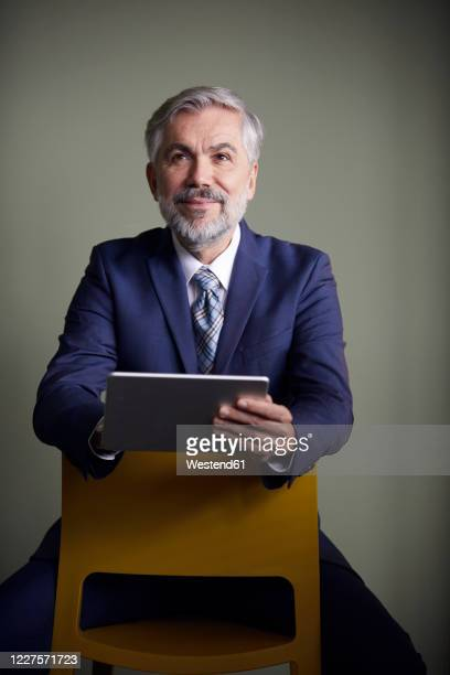 portrait of mature businessman sitting on a chair using tablet - 55 59 anni foto e immagini stock