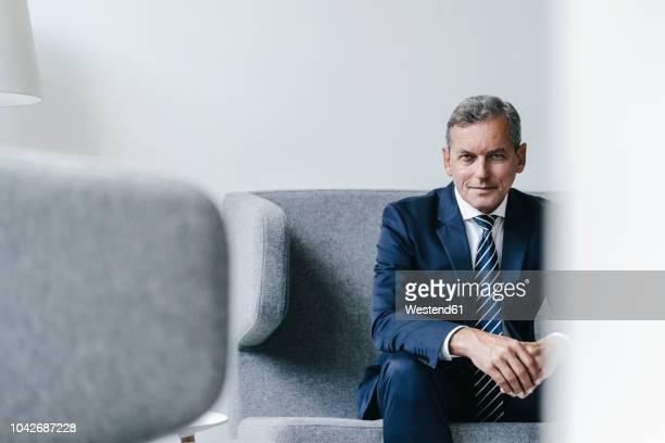 portrait of mature businessman sitting on couch in his office - geschäftsmann stock-fotos und bilder