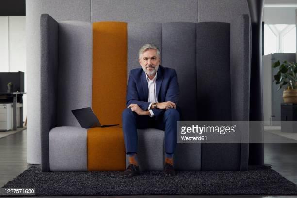 portrait of mature businessman sitting on couch in office - sitzen stock-fotos und bilder