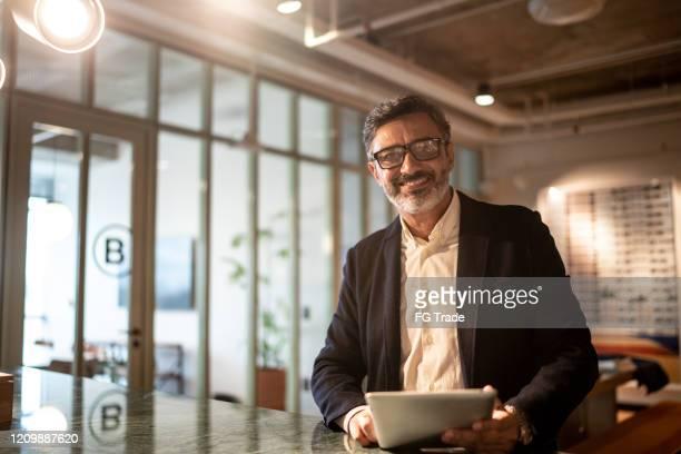 職場でデジタルタブレットを使用して座っている成熟したビジネスマンの肖像画 - 金融関係の職業 ストックフォトと画像