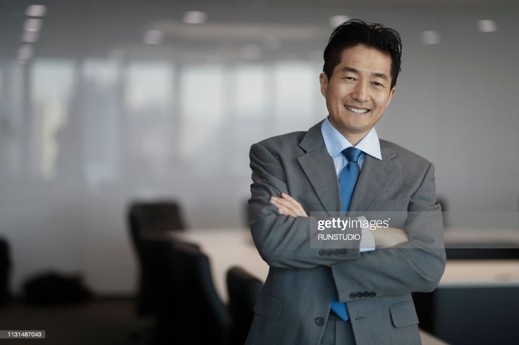 Portrait of mature businessman standing in conference room : ストックフォト