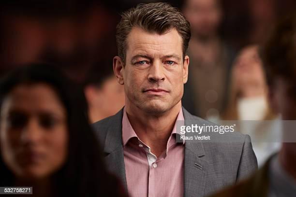 Portrait of mature businessman, standing in crowd