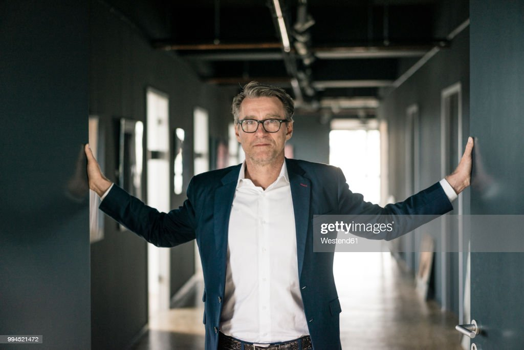 Portrait of mature businessman standing on office floor : Stock Photo
