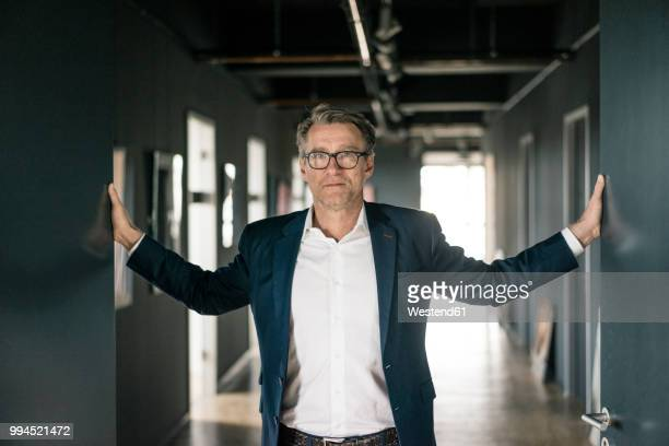 portrait of mature businessman standing on office floor - openmaken stockfoto's en -beelden