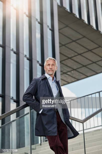 Portrait of mature businessman standing on stairs in front of modern office building looking at distance