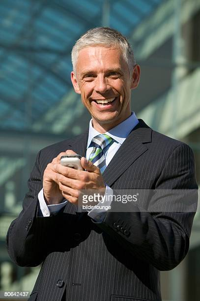 portrait of mature businessman typing text message on mobile phone