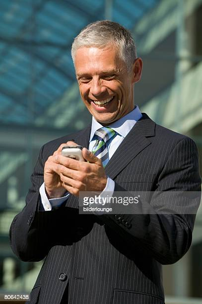 portrait of mature businessman typing text message on mobile phone - phone message stock pictures, royalty-free photos & images