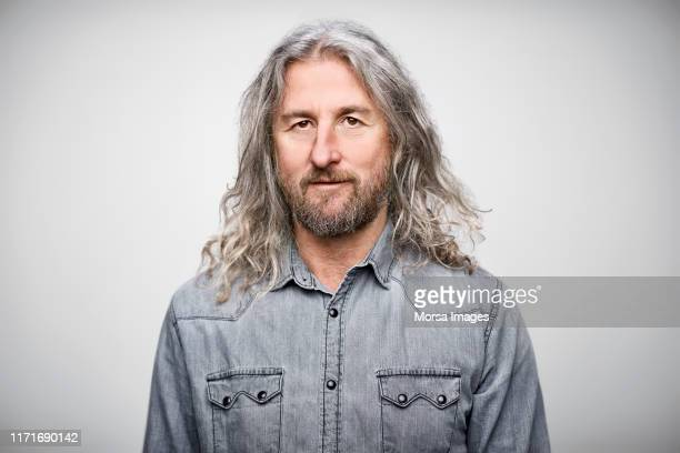 portrait of mature businessman wearing denim shirt - langes haar stock-fotos und bilder
