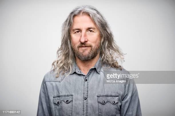 portrait of mature businessman wearing denim shirt - lang haar stockfoto's en -beelden