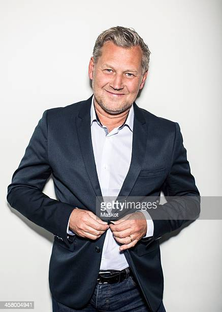 Portrait of mature businessman wearing suit while standing against wall
