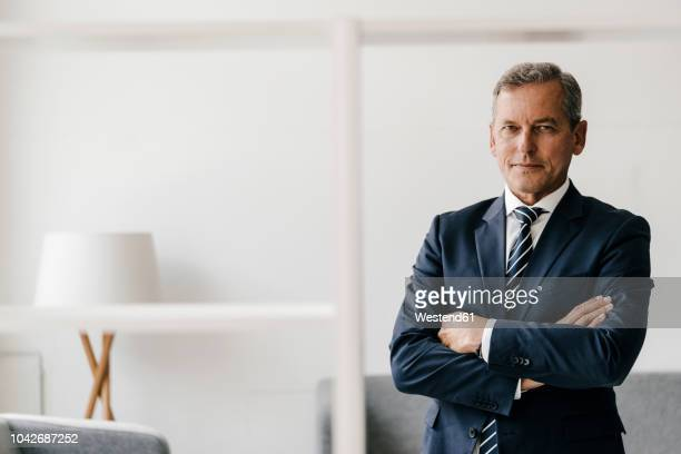 portrait of mature businessman with arms crossed in his office - arme verschränkt stock-fotos und bilder