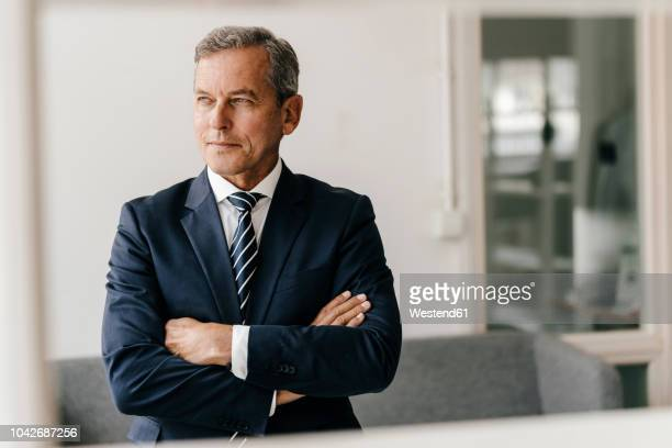 portrait of mature businessman with arms crossed in his office - respekt stock-fotos und bilder